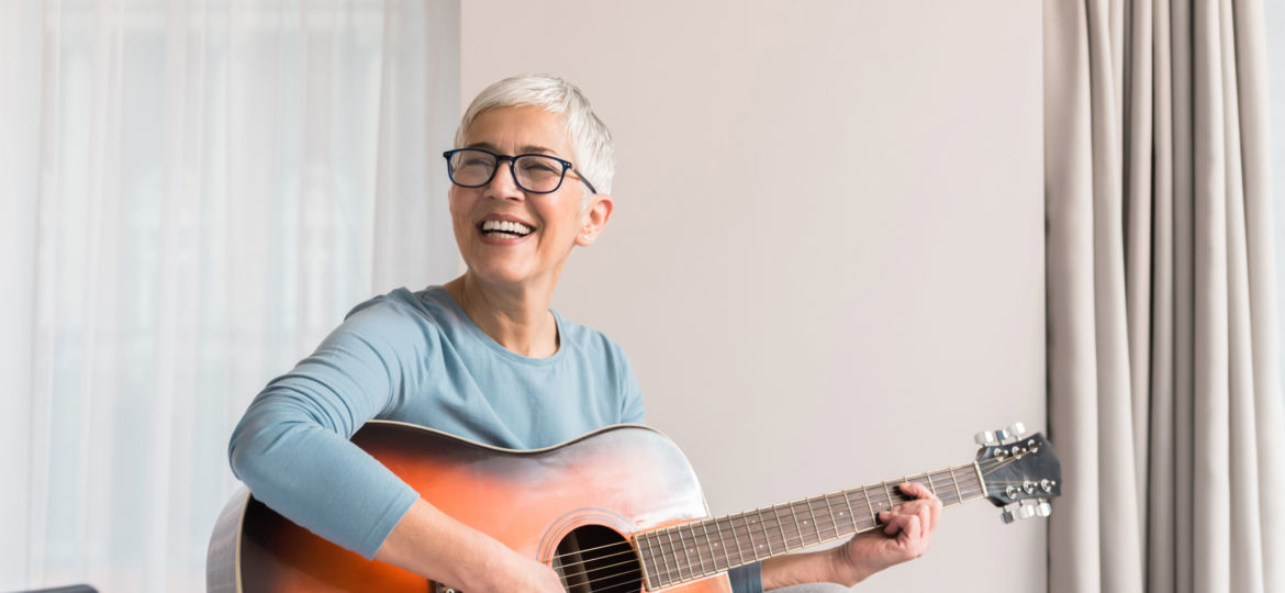 Smiling woman playing guitar
