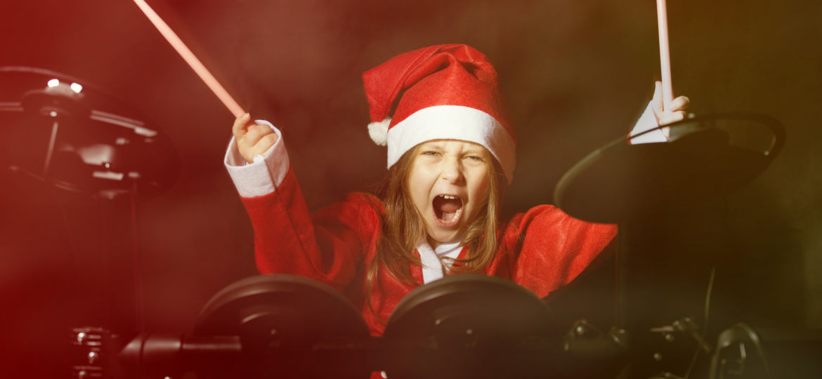 Little drummer disguised as Santa Claus playing the electronic drum kit